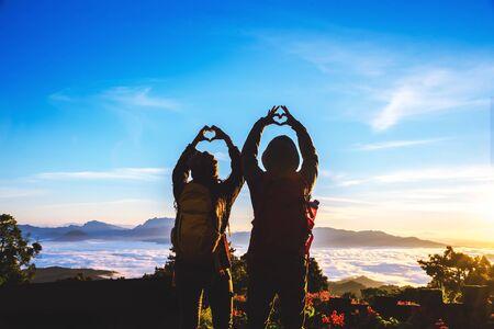 Les femmes et les hommes asiatiques amoureux voyagent se détendent pendant les vacances. Levez-vous pour le lever du soleil sur la montagne, joyeuse lune de miel, Leva la main pour faire une forme de cœur.