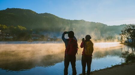 Asian woman and Asian man which backpacking standing near the lake, she was smiling, happy and enjoying the natural beauty of the mist.