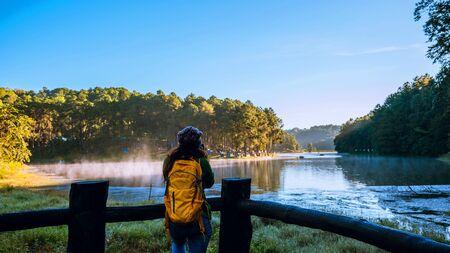 Young women Enjoying tourism take pictures nature, watching the beautiful lake in Thailand. 版權商用圖片 - 127640865