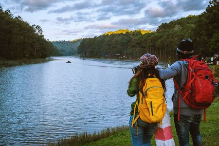 Happy couples with natural tourism, standing admire the beautiful landscape the Pang Ung lake, Mae Hong Son in Thailand.
