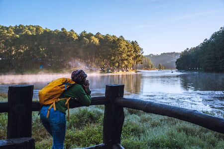 Young women Enjoying tourism take pictures nature, watching the beautiful lake in Thailand. 版權商用圖片