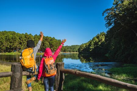 Couples travelers with backpack happy to relax on a holiday, travelers Pang-Ung park travel,Travel to visit nature landscape the beautiful at lake, at Mae-hong-son, in Thailand.