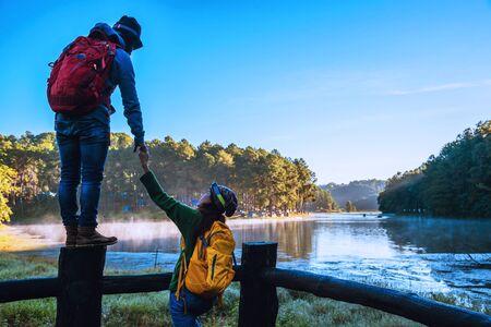 Young couple happy Enjoying nature tourism, watching the beautiful lake.