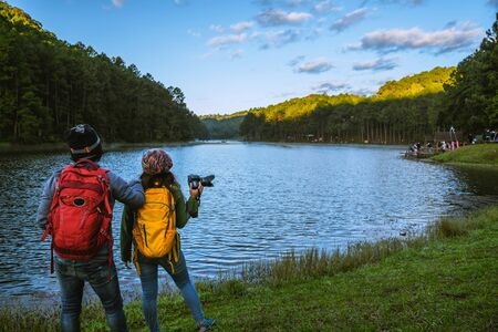 Couples asian Travel, take pictures of nature landscape the beautiful at Pang Ung lake, Mae Hong Son in Thailand.