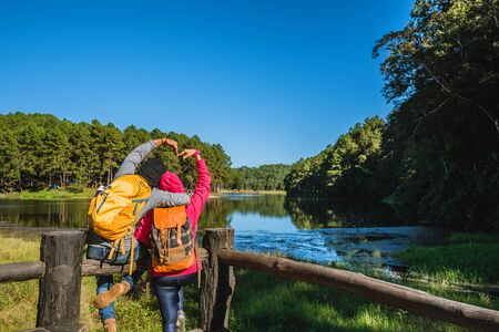 A Couple travelers with backpack standing on top Of the viewpoint nature a beautiful, Enjoy the sunrise on the foggy lake surface, Young men and Asian girlfriends travel nature on mountain Pang Ung park in Thailand. Banco de Imagens