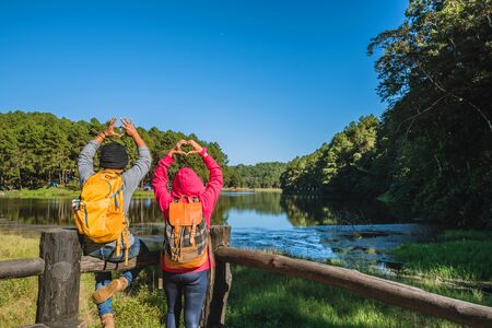 Couples travelers with backpack happy to relax on mountain, with lakes, beautiful ponds pine forests. couples raise their hands to make a heart shape. Happy and sweet love. 版權商用圖片