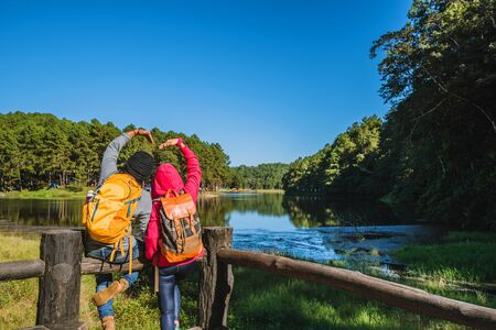 Couples travelers with backpack happy to relax on mountain, with lakes, beautiful ponds pine forests. couples raise their hands to make a heart shape. Happy and sweet love. Banco de Imagens