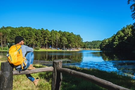 Young men travel in nature in the mountains, with lakes, beautiful ponds. Traveler with backpack standing on top Of the lake viewpoint, tourism to relax during the holidays.