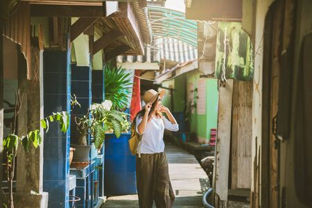 Asian women nature tourism, walking in the community old wooden houses, colorful houses. tourism, summer, holiday, travel Thailand. backpack, Nature, Travel, holiday.