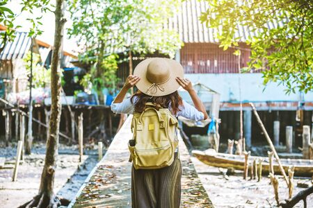 Asian woman travel nature Walk and watch the way of life of the villagers in rural villages fisherman. tourism, summer, lake, holiday, travel Thailand. backpack, Nature, Travel, holiday 版權商用圖片