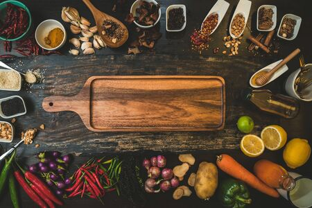 Spices for use as cooking ingredients on a wooden background with Fresh organic vegetables on wood. Healthy food herbs and spices. Organic vegetables on rustic wood. Banco de Imagens