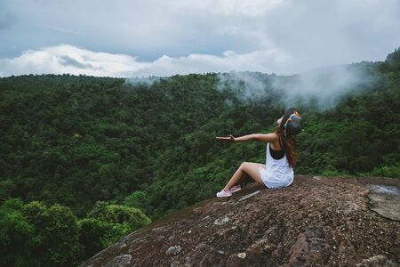 Asian woman travel nature. Travel relax. Freedom happy traveler woman standing with raised arms and enjoying a beautiful nature on peak of foggy mountain.