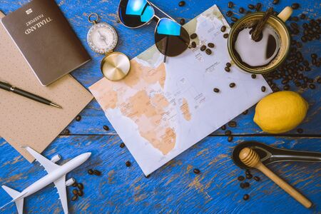 accessories for the traveler on the old background on the on blue wood table. Travel concept using world map and compass along with other travel accessories. Hot coffee and beans. summer 版權商用圖片