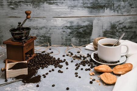 Coffee cup, with coffee grinder and coffee beans with ground powder on table. Top view Hot coffee and pastries on a old kitchen table. background concept Coffee cup and coffee grinder with other accessories.