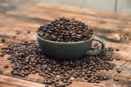 Cup full of Black coffee grains lie on a brown wooden table, background image. Coffee beans in a green cup. Фото со стока
