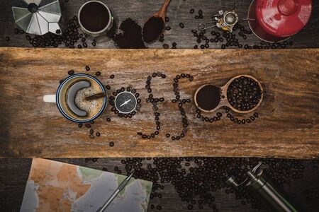equipment material about coffee beans. Top view with copy space for your text. Coffee message write on a wooden table. Concept travel with map.