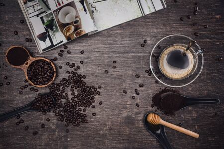 Brown coffee beans And a cup of hot coffee placed on a wooden table with honey. Wooden background and espresso and beans. Top view with copy space for your text. Books about coffee.