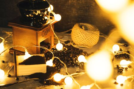 coffee grinder and coffee beans with ground powder on table. Side view Hot coffee and pastries on old kitchen table rustic. with led string lights.