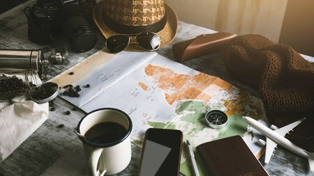 Tourist planning vacation with the help of world map and compass along and Coffee cup with coffee grinder with other travel accessories. Preparing for travel. Travel planning concept holiday with map. summer.