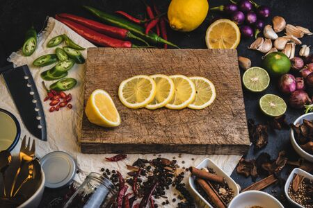 Healthy food herbs. Spices for use as cooking ingredients on a wooden table with Fresh organic vegetables and raw material with Variety on the rustic table. Sliced ​​lemon on a wooden cutting board.