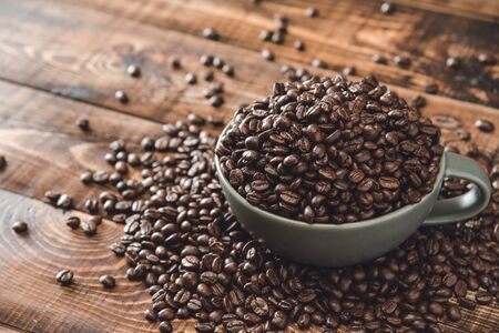 Cup full of Black coffee grains lie on a brown wooden table, background image. Coffee beans in a green cup. 版權商用圖片