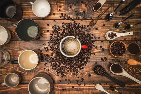 Many cups of coffee with beans on wooden table, top view. Flat lay composition with cups of coffee on background Old wood grain. Food photography, beverage.