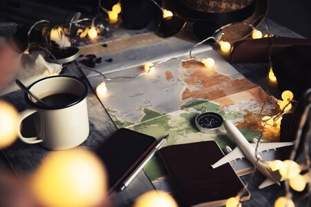 Tourist planning vacation with the help of world map and compass along and Coffee cup with coffee grinder with other travel accessories and led string lights. Preparing for travel. Travel planning concept holiday. summer. Фото со стока