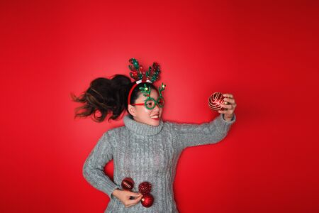 Christmas New Year. Young Woman dressed in warm sweater with  Props ball red with christmas ornaments in Holiday on shine red background. Concept merry christmas. Banco de Imagens