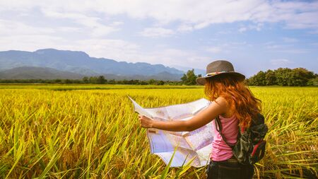 Asian women travel Rice fields Golden yellow On the mountains in the holiday. Travel with a map of Asian girls. Nature travel relax summer