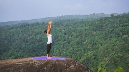 Asian women relax in the holiday. Play if yoga. On the Mountain rock cliff. Nature of mountain forests in Thailand. Young woman practicing yoga in the nature female happiness. exercise yoga Banco de Imagens