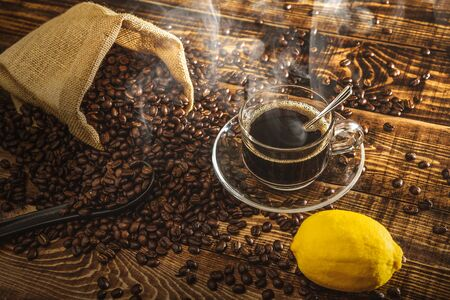 Coffee cup and beans on old kitchen table. Top view with copy space for your text. coffee bag and with lemons on wooden table. Black coffee beans. Espresso