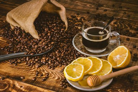Coffee cup and beans on old kitchen table. Top view with copy space for your text. coffee bag and with sliced lemons on wooden table. Black coffee beans.