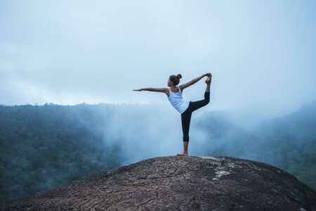 Young woman exercises yoga in the mountains. Asian woman travel nature. Travel relax exercises yoga touch natural fog on mountain peak.