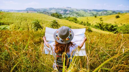 Asian women travel relax in the holiday. Stand natural touch mountain field summer. View map travel explore. In Thailand