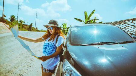 woman travel relaxing nature mountain map navigation. Travel relax in the holiday. View map travel explore. The girl standing view map travel explore beside the car. In Thailand 写真素材