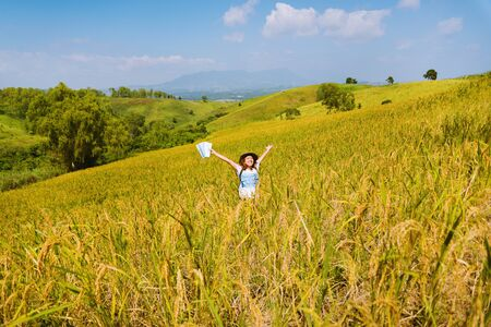 Asian women travel Rice fields Golden yellow On the mountains in the holiday. happy and enjoying a beautiful nature. Rice fields Golden. Travel with a map of Asian girls. summer