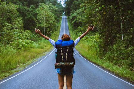 Freedom traveler woman standing with raised arms and enjoying a beautiful nature On a country road. woman with backpack travel In the countryside On a mountain.