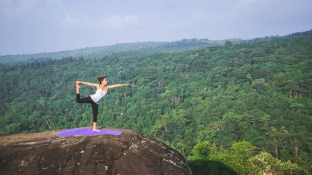 Asian women relax in the holiday. Play if yoga. On the Mountain rock cliff. Nature of mountain forests in Thailand. Young woman practicing yoga in the nature female happiness. exercise yoga 写真素材