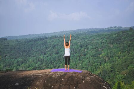 Asian women relax in the holiday. Play if yoga. On the Moutain rock cliff. Nature of mountain forests in Thailand. Young woman practicing yoga in the nature female happiness. exercise yoga 写真素材