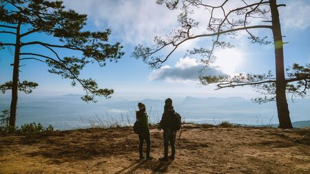Asian lover women and men travel nature. Travel relax. landscapes on the cliff. At sunrise which has fog guard. Lovers travel in the mountains. travel Thailand.