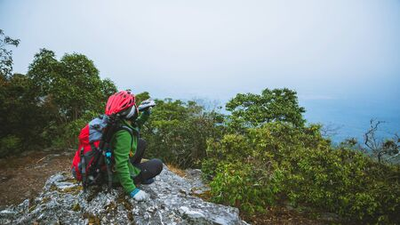 Asian woman travel nature. Travel relax. Sit and watch nature landscapes on the cliff. Vacation on the mountains. 写真素材