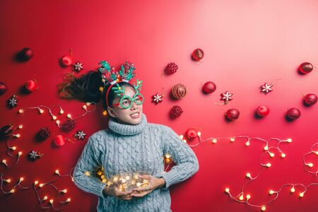 Christmas New Year. Young Woman dressed in warm sweater with  Props ball red with christmas ornaments in Holiday on shine red background. Concept merry christmas. 写真素材