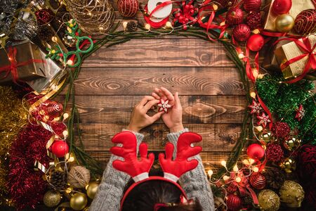 Girl laying Christmas flat composition on the wooden background with copy space for your text. Merry Christmas and Happy New Year.