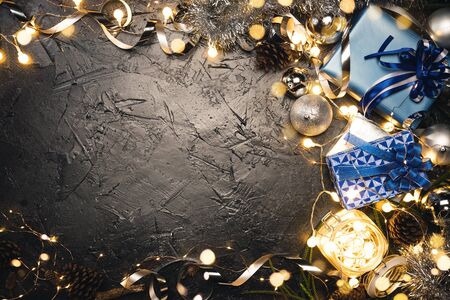 Christmas gift with blue ribbon and Christmas decoration balls on abstract bokeh black background with copy space. Holiday background greeting card for Merry Christmas and New Year.