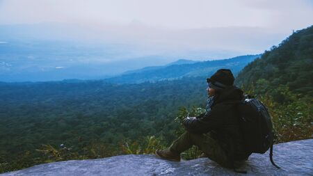 Asian man travel nature. Travel relax. Sit and watch nature landscapes on the cliff. Vacation on the mountains. Admire the atmosphere landscape on travel Thailand. 写真素材