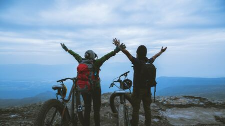 Asian lover women and men Travel Nature. Travel relax ride a bike Wilderness in the wild. Standing on a rocky cliff. travel Thailand  写真素材