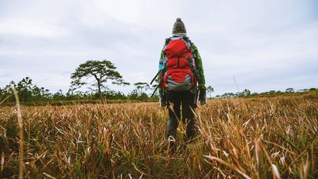 Asian woman travel nature. Travel relax. Standing natural touch grass on the Mountain. Girl with a backpack Walking in the grass forest. travel nature. Travel relax. 写真素材