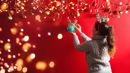 Merry Christmas and Happy New Year.The girl is designing with Holiday ornaments decoration. the christmas background red. with copy space for your text. Led lights