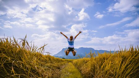 Asian women travel Rice fields Golden yellow On the mountains in the holiday. happy and enjoying a beautiful nature. travelling in countryside, Green rice fields, Travel Thailand.