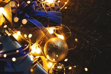 Christmas gift with blue ribbon and Christmas decoration balls on abstract bokeh black background with copy space and decorative LED lights. Merry Christmas and New Year.